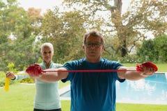 Couples supérieurs actifs s'exerçant avec la bande de résistance en porche à la maison images stock