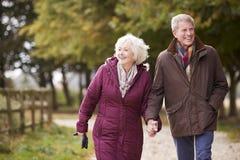 Couples supérieurs actifs sur la campagne d'Autumn Walk On Path Through photographie stock libre de droits