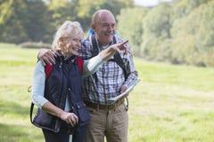 Couples supérieurs actifs sur la promenade dans la campagne ensemble Photos libres de droits
