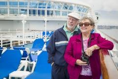 Couples supérieurs actifs utilisant des jumelles sur la plate-forme d'un bateau de croisière Photographie stock libre de droits