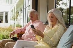 Couples supérieurs actifs utilisant le téléphone portable et lire un livre dans le porche photos libres de droits
