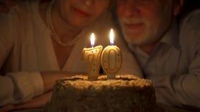 Couples supérieurs affectueux célébrant l'anniversaire 70s avec le gâteau à la maison dans la soirée Soufflage des bougies banque de vidéos