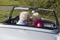 Couples supérieurs affectueux dans la voiture de sport de vintage Image stock