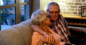 Couples supérieurs agissant l'un sur l'autre entre eux sur le sofa 4k banque de vidéos