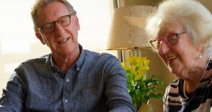 Couples supérieurs agissant l'un sur l'autre les uns avec les autres à la table de salle à manger 4k clips vidéos