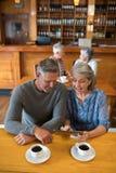 Couples supérieurs agissant l'un sur l'autre tout en à l'aide du comprimé numérique Photos libres de droits