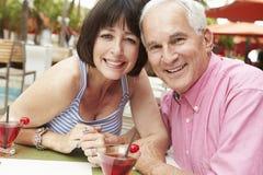 Couples supérieurs appréciant des cocktails dans la barre extérieure ensemble Photos stock