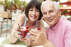 Couples supérieurs appréciant des cocktails dans la barre extérieure ensemble Image libre de droits