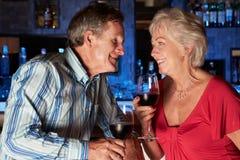 Couples supérieurs appréciant la boisson dans la barre Photos stock