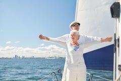 Couples supérieurs appréciant la liberté sur le bateau à voile en mer images libres de droits