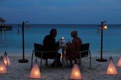 Couples supérieurs appréciant le défunt repas dans le restaurant extérieur photo stock