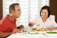 Couples supérieurs appréciant le repas à la maison Photographie stock libre de droits