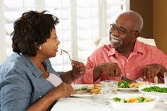 Couples supérieurs appréciant le repas à la maison Photos stock