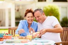 Couples supérieurs appréciant le repas dans le jardin ensemble Photos libres de droits