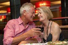 Couples supérieurs appréciant le repas dans le restaurant Photo stock