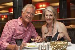 Couples supérieurs appréciant le repas dans le restaurant Photo libre de droits