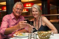 Couples supérieurs appréciant le repas dans le restaurant Images libres de droits