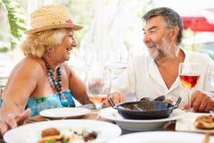 Couples supérieurs appréciant le repas dans le restaurant extérieur Images stock