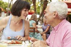 Couples supérieurs appréciant le repas dans le restaurant extérieur ensemble Photos libres de droits