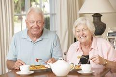 Couples supérieurs appréciant le repas ensemble à la maison Image libre de droits