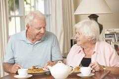 Couples supérieurs appréciant le repas ensemble à la maison Image stock
