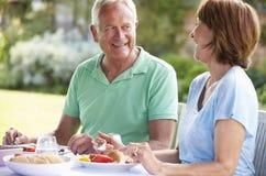 Couples supérieurs appréciant le repas extérieur ensemble Image libre de droits