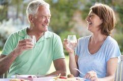 Couples supérieurs appréciant le repas extérieur ensemble Image stock