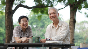 Couples supérieurs asiatiques faisant la pause d'apprendre des actions d'investissement Photos stock