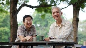 Couples supérieurs asiatiques faisant la pause d'apprendre des actions d'investissement Images stock