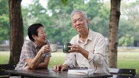 Couples supérieurs asiatiques faisant la pause d'apprendre des actions d'investissement Image stock