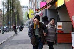 Couples supérieurs asiatiques marchant le long de la rue de l'Europe tout en voyageant Images stock