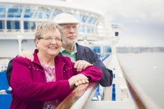 Couples supérieurs attrayants appréciant la plate-forme d'un bateau de croisière Photographie stock
