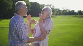 Couples supérieurs attrayants riant sur la pelouse verte banque de vidéos