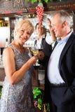 Couples supérieurs au bar avec la glace de vin à disposition Photo stock