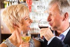 Couples supérieurs au bar avec la glace de vin à disposition Images stock