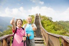couples supérieurs augmentant sur la montagne avec des pouces  Photos libres de droits