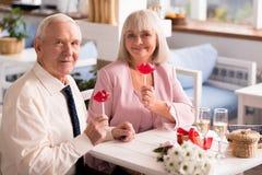 Couples supérieurs avec du charme posant avec des sucreries Photo stock