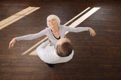 Couples supérieurs avec plaisir tangoing dans le studio de danse Photo stock