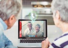 Couples supérieurs ayant l'appel visuel avec des amis sur l'ordinateur portable Images libres de droits