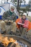 Couples supérieurs ayant la nourriture au feu de camp Images stock
