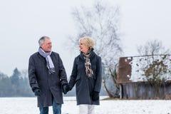 Couples supérieurs ayant la promenade en hiver photos libres de droits