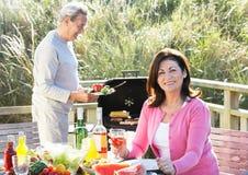 Couples supérieurs ayant le barbecue extérieur Images libres de droits