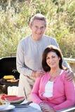 Couples supérieurs ayant le barbecue extérieur Photos stock