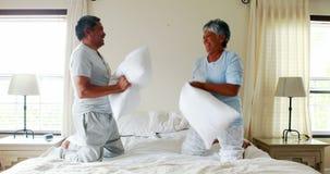 Couples supérieurs ayant le combat d'oreiller sur le lit 4k banque de vidéos