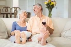 Couples supérieurs ayant le maïs éclaté et le verre de vin dans le salon Photographie stock