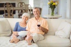 Couples supérieurs ayant le maïs éclaté et le verre de vin dans le salon Photographie stock libre de droits