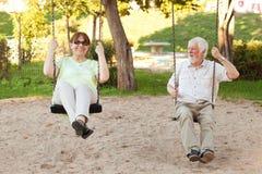 Couples supérieurs balançant en parc photographie stock
