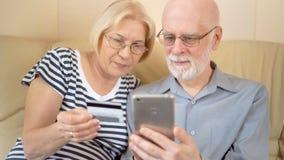 Couples supérieurs beaux gais se reposant sur le sofa Achat en ligne avec la carte de crédit sur le smartphone banque de vidéos