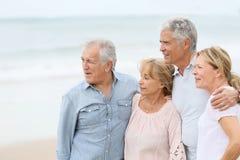 Couples supérieurs beaux marchant sur la plage Images libres de droits