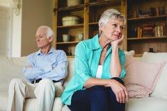 Couples supérieurs bouleversés s'ignorant dans le salon Images stock
